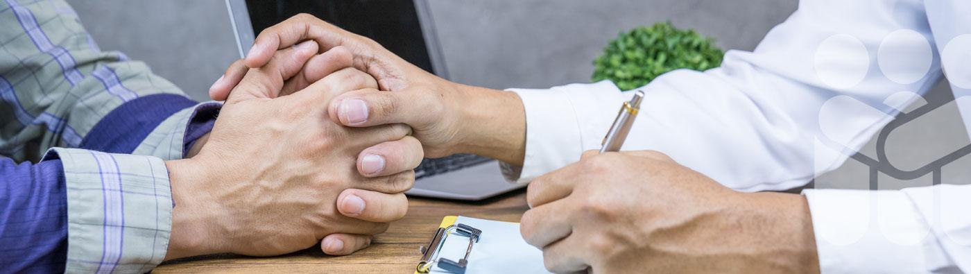 Vielfalt Pflegen Headerbild Kontakt: Nahaufnahme einer gefalteten Hand auf der linken Bildseite. Die rechte Hand einer Pflegefachperson umfasst vertrauensvoll die gefalteten Hände. Mit der linken Hand dokumentiert die Pflegekraft auf einen Anamnesebogen.